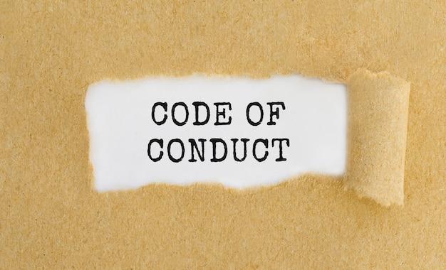 Tekst kodeksu postępowania widoczny za podartym brązowym papierem.