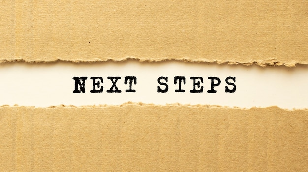Tekst kolejne kroki za podartym brązowym papierem