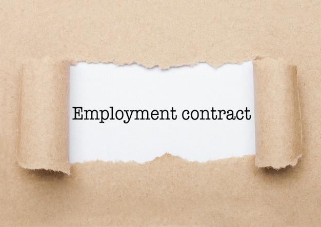 Tekst koncepcji umowy o pracę pojawiający się za podartą kopertą z brązowego papieru