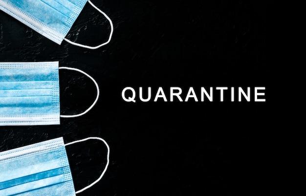 Tekst kwarantanny. maski ochronne na twarz przed bakteriami na czarnym tle. atak wirusa, koncepcja opieki zdrowotnej. niebezpieczny koronawirus. leczenie medyczne.