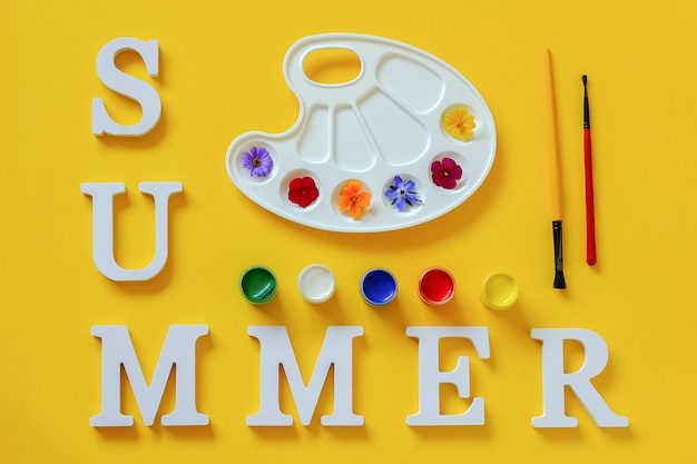Tekst lato, jasne kolorowe kwiaty na artystycznej palecie, pędzel i gwasz. kolory latem koncepcja kreatywnych