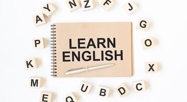 Tekst learn english na notatniku w kolorze rzemieślniczym z drewnianymi kostkami