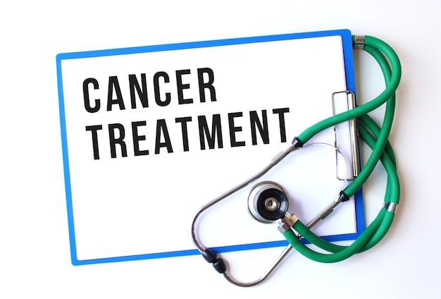 Tekst leczenia raka na folderze medycznym z dokumentami i stetoskopem na białym tle. pojęcie medyczne.