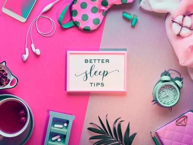 """Tekst """"lepsze wskazówki dotyczące snu"""" w ramce. koncepcja zdrowego snu. maska do spania, budzik, słuchawki, zatyczki do uszu, herbata i pigułki."""