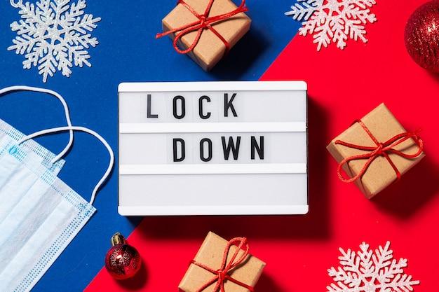 Tekst lockdown na lightboxie na dwukolorowym czerwonym i niebieskim tle z dekoracjami świątecznymi