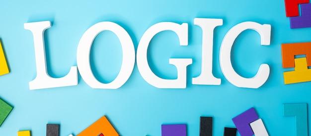Tekst logiki z kolorowymi drewnianymi puzzlami, blok geometryczny kształt na niebieskim tle. koncepcje logicznego myślenia, zagadka, rozwiązania, racjonalność, strategia, światowy dzień logiki i edukacja