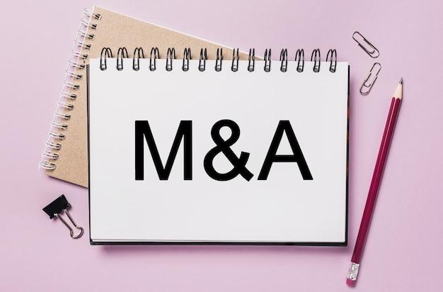 Tekst m i a na białej naklejce z tłem materiałów biurowych. mieszkanie leżało na koncepcji biznesu, finansów i rozwoju