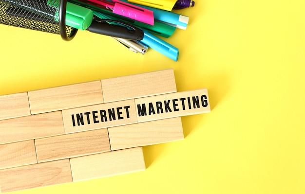 Tekst marketingu internetowego na drewnianym bloku na żółtym tle z papeterią biurową