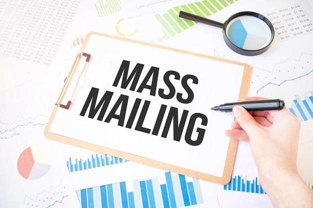 Tekst masowej wysyłki na białej kartce papieru i znacznik na dłoni biznesmena na schemacie.