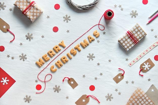 Tekst merry christmas wykonany z liter cookie. kreatywne mieszkanie świąteczne z pudełkami na prezenty i dekoracjami wykonanymi z papieru rzemieślniczego.