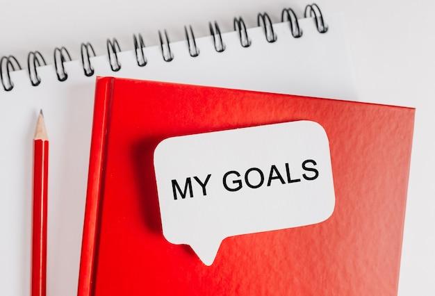 Tekst moje cele białą naklejkę na czerwonym notatniku z tłem biurowym. mieszkanie leżało na koncepcji biznesu, finansów i rozwoju