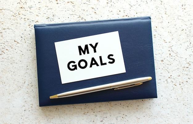Tekst moje cele na wizytówce leżącej na niebieskim notesie obok długopisu. pomysł na biznes.