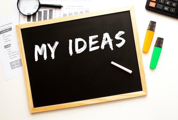 Tekst moje pomysły zapisane kredą na tablicy łupkowej. biurko z materiałami biurowymi. pomysł na biznes.