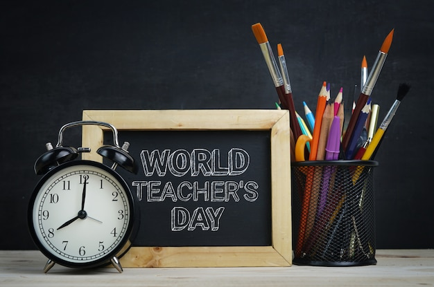 Tekst na temat światowego dnia nauczyciela. drewniana tablica, szkolna stacjonarna i budzik