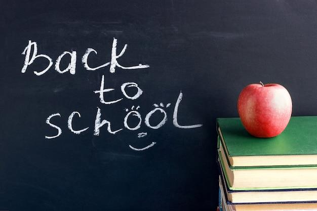 Tekst napis z powrotem do szkoły na czarnej tablicy i czerwone jabłko na podręczników książek stosu
