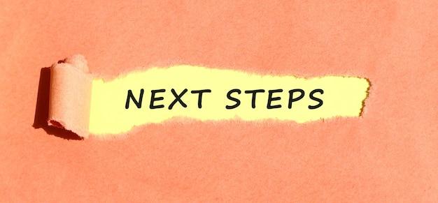 Tekst następne kroki pojawiający się na żółtym papierze za podartym kolorowym papierem. widok z góry.