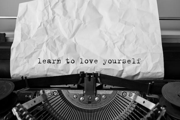 Tekst naucz się kochać siebie wpisanego na maszynie do pisania w stylu retro