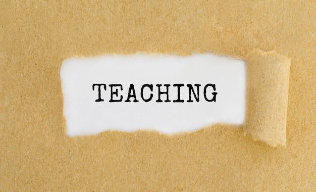 Tekst nauczania pojawiający się za podartym brązowym papierem.