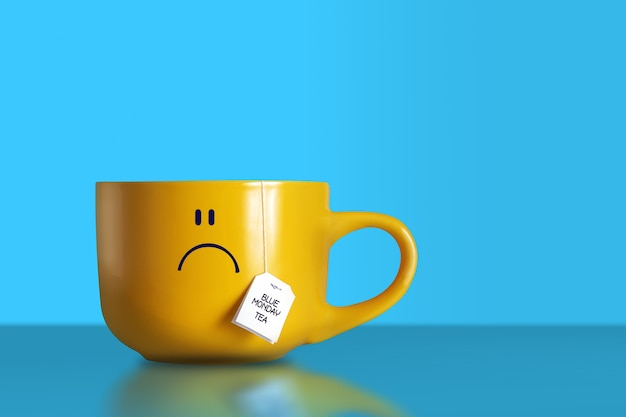 Tekst niebieski herbaty poniedziałek ze smutną buźką na dużym żółtym kubku na niebieskim tle. skopiuj miejsce.