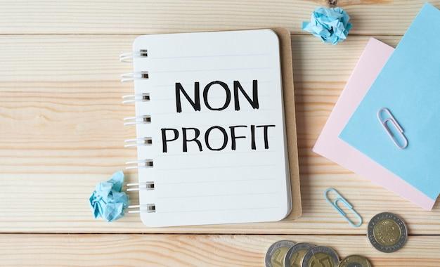 Tekst non profit na naklejkach. schowek z wykresami, długopisem, skarbonką i kalkulatorem na niebieskim tle. widok ogólny koncepcji rachunkowości.