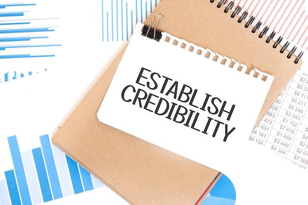 Tekst określ wiarygodność na białej kartce i notatnik z brązowego papieru na stole ze schematem. pomysł na biznes