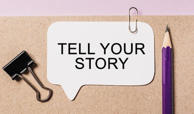 Tekst opowiedz swoją historię na białej naklejce z tłem biurowym. mieszkanie leżało na koncepcji biznesu, finansów i rozwoju
