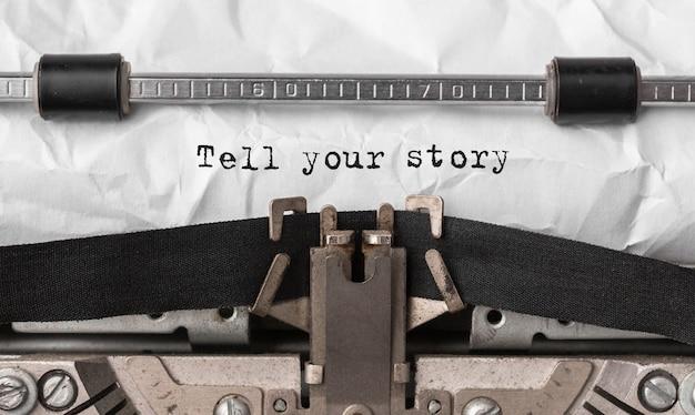 Tekst opowiedz swoją historię wpisany na maszynie do pisania w stylu retro