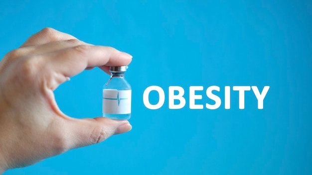 Tekst otyłości w dłoni mężczyzny trzymającego fiolkę z lekiem na uzdrowienie