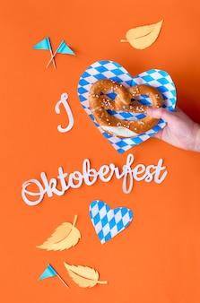 """Tekst papierowy """"kocham oktoberfest"""", leżał płasko na żywym pomarańczowym papierze z preclem w ręku"""