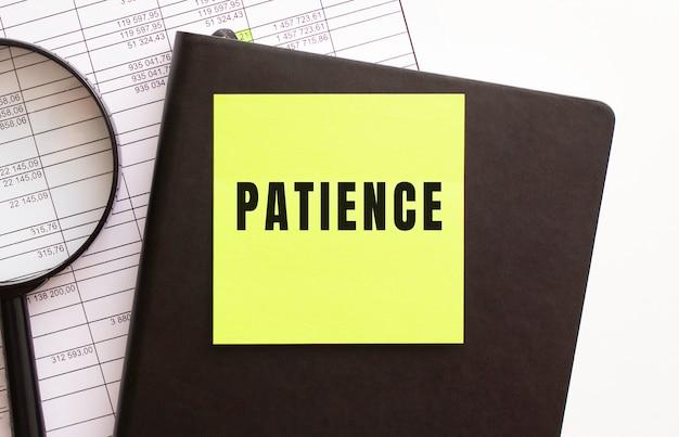 Tekst patience na naklejce na pulpicie. pamiętnik i lupa.