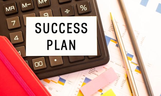 Tekst plan sukcesu na białej karcie z metalowym długopisem, kalkulatorem i wykresami finansowymi