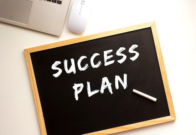Tekst plan sukcesu napisany kredą na tablicy łupkowej. biurko. pomysł na biznes.