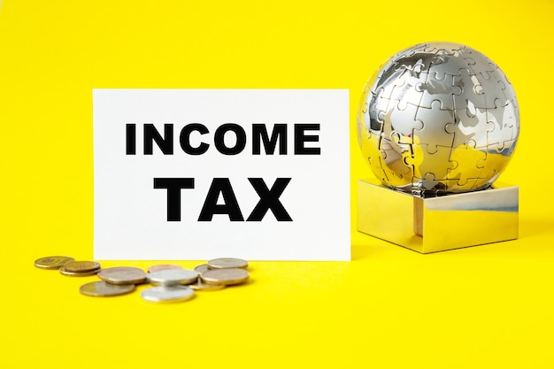 Tekst: podatek dochodowy. glob i drewniane kostki na żółtym tle. pojęcie światowego biznesu, marketingu, finansów.