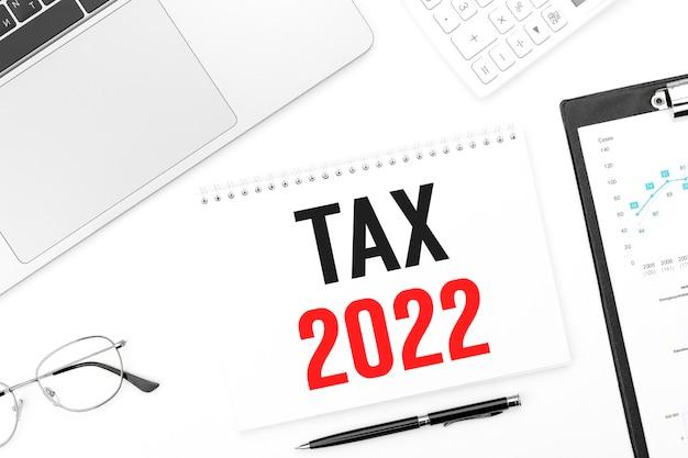 Tekst podatk 2022 na karcie. laptop, okulary, długopis, kalkulator i schowek z wykresami i wykresami. plan biznesowy. widok z góry.