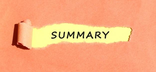 Tekst podsumowanie umieszczony na żółtym papierze za podartym kolorowym papierem. widok z góry.