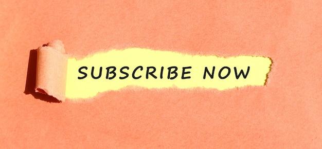 Tekst pojawiający się na żółtym papierze za podartym kolorowym papierem.