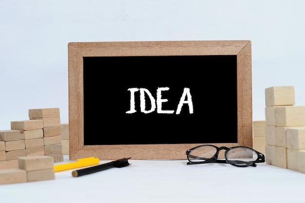 Tekst pomysłu na tablicy i bloku drewna