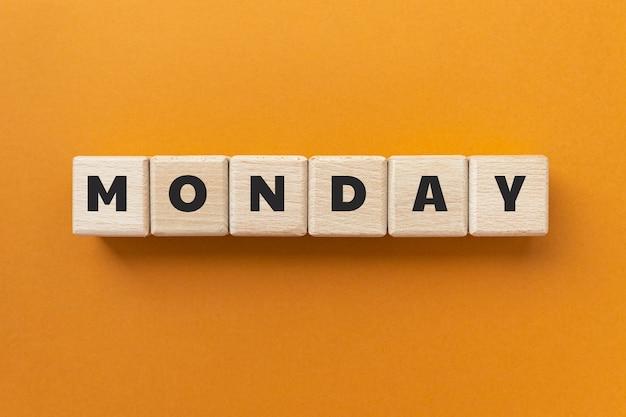 Tekst poniedziałek na drewnianych kostkach na pomarańczowym tle. dzień tygodnia. kwadratowe klocki drewniane. widok z góry, układ płaski.