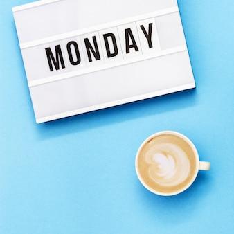 """Tekst """"poniedziałek"""" na lightbox i filiżankę kawy na wakacje. początek koncepcji tygodnia roboczego. widok z góry na niebieskim tle."""