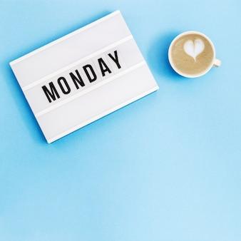 """Tekst """"poniedziałek"""" na lightboxie i filiżance kawy z piankowym sercem"""