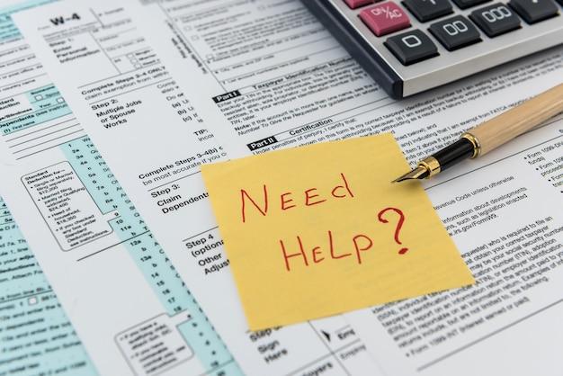 Tekst potrzebuje pomocy lub czasu podatkowego na naklejce leżącej w innym formularzu podatkowym. papierkowa robota