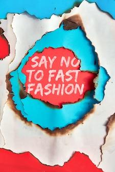 """Tekst """"powiedz nie szybkiej modzie"""" w otworze wypalonym przez kolorowy papier"""