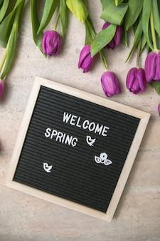 Tekst powitania wiosny na tablicy i bukiet fioletowych tulipanów
