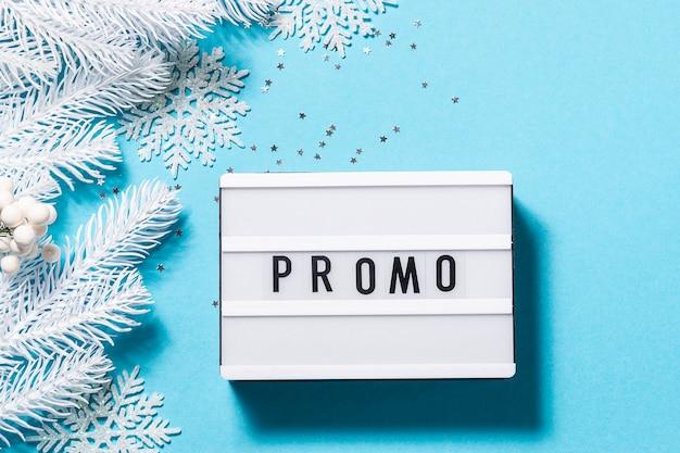 Tekst promo na lightboxie na niebieskim tle z pięknymi białymi dekoracjami świątecznymi
