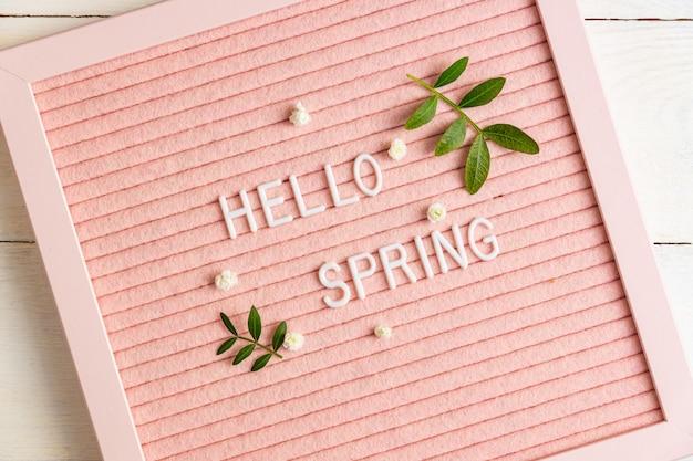 Tekst przywitaj wiosnę na różowej tablicy z zielonymi gałązkami i kwiatami łyszczec na drewnianym tle, kompozycja w stylu minimalizmu, miejsce na tekst.