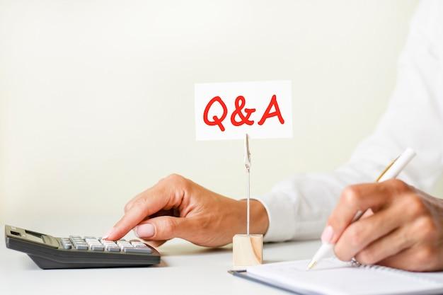 Tekst q i a napisany na białej kartce papieru zaciśniętej w uchwycie na papier. w tle dłonie kobiety piszące długopisem na papierze i kalkulator dotykowy