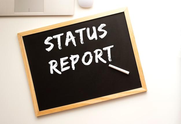 Tekst raport statusu napisany kredą na tablicy łupkowej. biurko. pomysł na biznes.