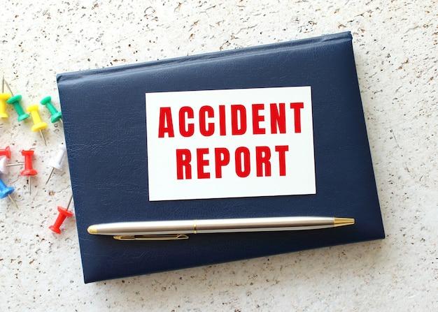 Tekst raport z wypadku na wizytówce leżącej na niebieskim zeszycie obok długopisu. pomysł na biznes.