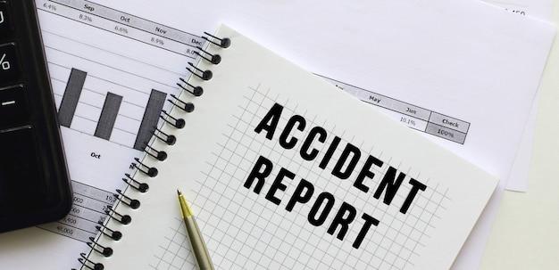 Tekst raportu wypadku na stronie notatnika leżącego na wykresach finansowych na biurku