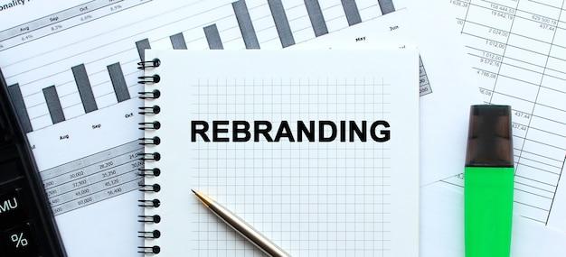 Tekst rebranding na stronie notatnika leżącego na wykresach finansowych.